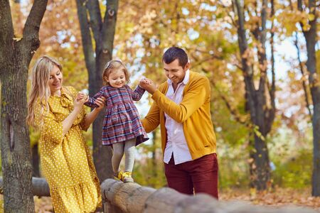 Happy family playing with baby in the park in autumn. Stockfoto