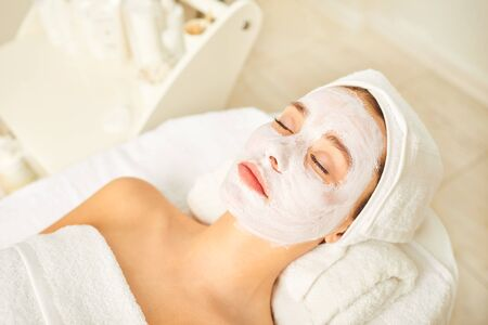 Cosmetic mask on the face of a woman lies in the spa salon at the reception at the beautician. A woman is relaxing in the spa salon. Stockfoto