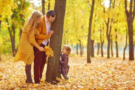 Side view of playful young parents and little girl around tree in beautiful golden autumnal park
