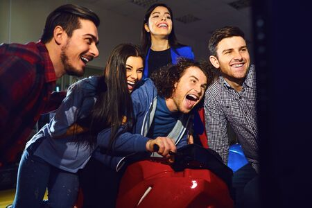 A group of friends playing arcade machine. in an amusement park. Young people have fun. Stock fotó