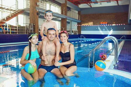 A happy family in a swimming pool indoors. Healthy lifestyle.