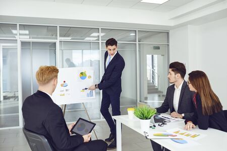 A group of young businessmen are listening to a coachs speech. Group of young business people standing at office. Teamwork concept. Meeting of young businessmen. Stockfoto