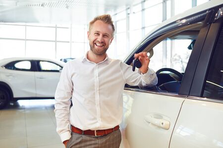 Happy buyer of a new car holds keys in his hand at a car dealership. Stockfoto