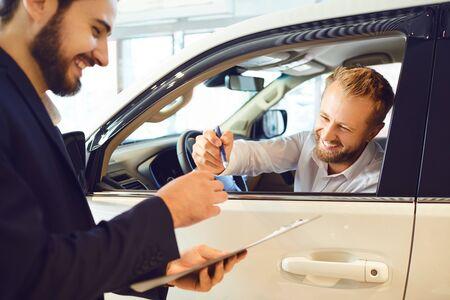 Młoda kobieta kupuje samochód w salonie samochodowym. Mężczyzna podpisuje umowę wynajmu samochodu.