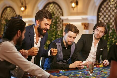 A young man is happy to win at the casino. A group of people playing poker roulette in a casino. Stockfoto