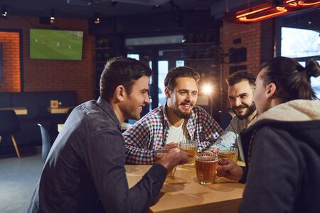 Friends talk, drink beer in a bar. Young people in a meeting in a pub. Stockfoto