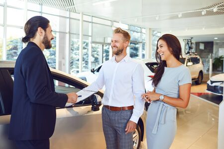 A car salesman and a buyer shake hands. A couple buys a car at a car dealership. Buying rental a car. Stockfoto