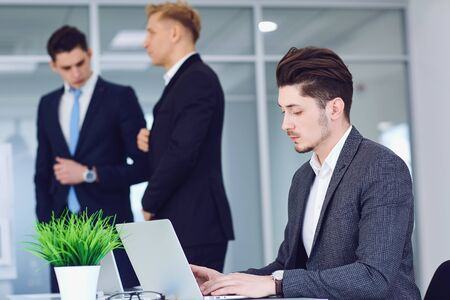 Serious young business people working at a table in an office. Business meeting of businessmen in a business center. Banque d'images - 129646026