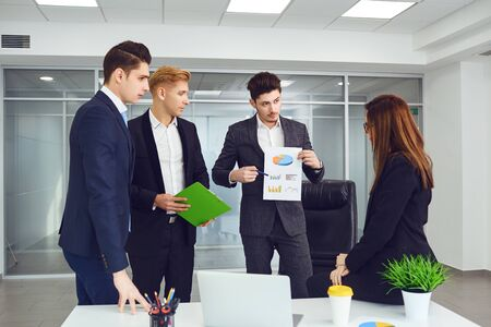 Group of young business people standing at office. Teamwork concept. Meeting of young businessmen.