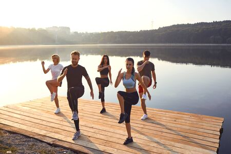 A group of active people do exercises in the park near the lake in the summer in autumn.Training a group of athletes in nature.