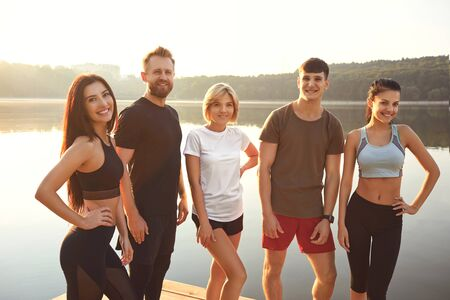 A group of young athletes are smiling standing on the background of a lake in a city park in autumn summer. Healthy lifestyle.