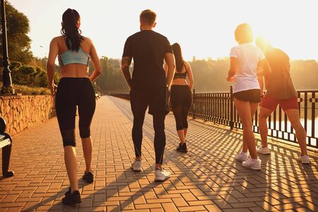 A group of young people in sportswear are running in the park. Back view. Stockfoto