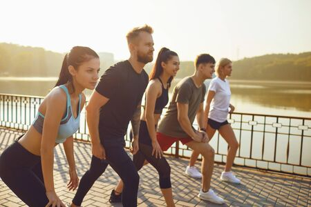 A group of athletes running in the park. Friends in sportswear portrait standing outdoors in the morning. Healthy lifestyle.