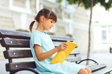 Little girl in a dress reads a book in her hands while sitting on a bench.