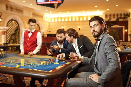A young brunette man in a suit with a glass of whiskey in his hand sitting at table roulette playing poker at a casino. Stok Fotoğraf