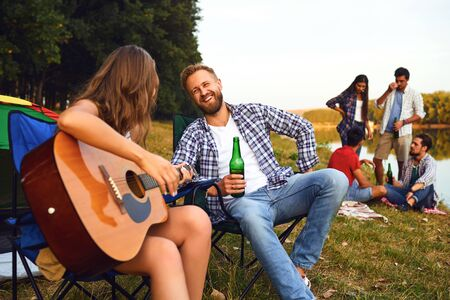 Friends with a guitar on a picnic with a tent on nature in the summer in autumn. Stock fotó