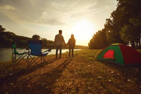 A hiker couple holding hands next to a tent by the lake at sunset in the summer in autumn.