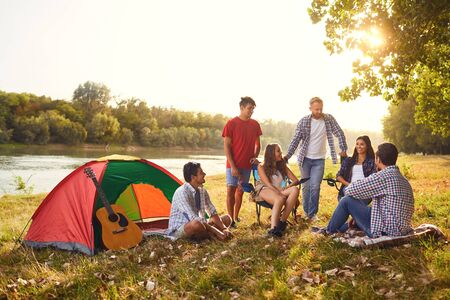 A group of friends have a picnic in a forest near a lake in the summer in autumn. Stock fotó