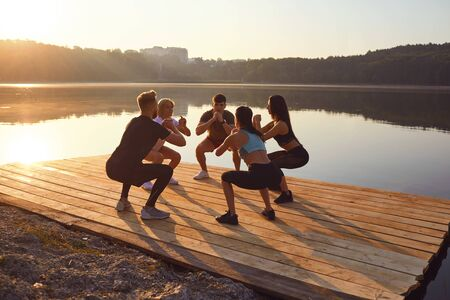 A group of sports people do squat exercises in a park by the lake in the summer in autumn. Training a group of athletes in nature.