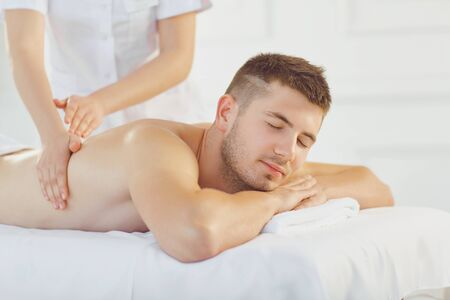 Young content man lying on table with eyes closed enjoying massage and relaxing in daylight Stock fotó