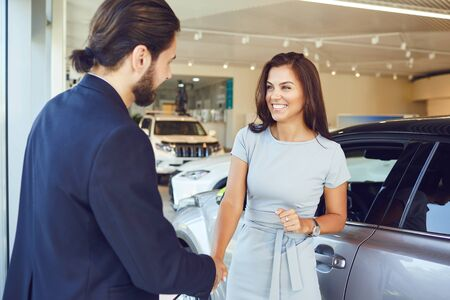 Girl buyer shakes hands dealer a car in a showroom.