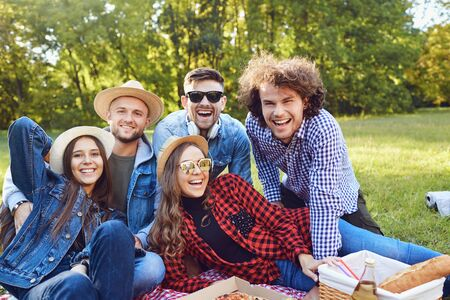 A group of people sitting on the grass on a picnic in the summer autumn park. Stock fotó
