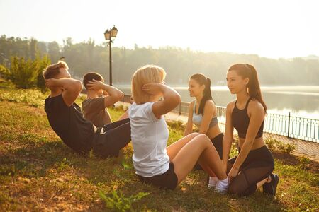 A group of people doing exercises sitting on the grass in the summer park in autumn. Athletes do abs in nature.