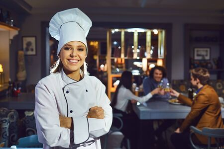 Woman chef in a restaurant. Cook girl smiling on the background of the cafe.