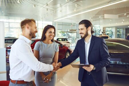 A couple buys a new car. A man and a car salesman make a handshake at a car dealership. Buying rental a car.