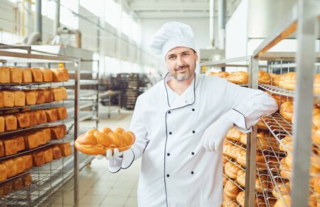 A baker, a man in white uniform, is standing in a bakery against the shelves of bread. Stock fotó
