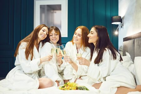 Young women in white bathrobe with champagne glasses at a spa party in a hotel room. Rest girlfriends at home.