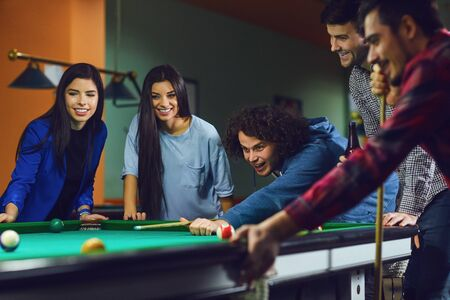 Friends play billiards in bar. A group of young people playing fun billiards.