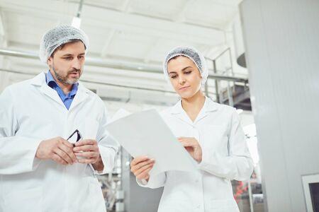 Dos tecnólogos con batas de laboratorio y máscaras controlan el proceso de producción en la fábrica. Foto de archivo
