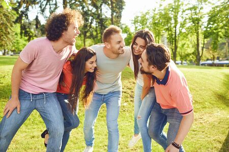 A group of friends laughing hugging in a park in nature.