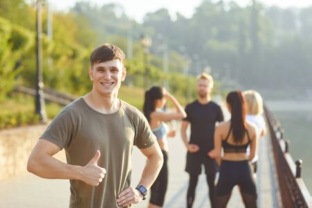 Young sporty guy smiles on the background of friends athletes in the park. Health. Healthy lifestyle.