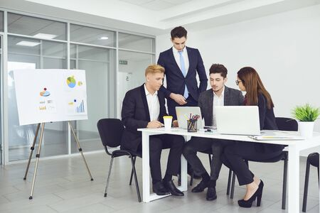 Serious young business people communicate at a table in an office. Business meeting of businessmen in a business center.