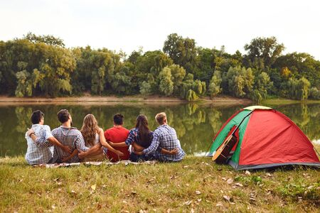 Group of people smiling standing on a picnic with a tent on the nature in the summer in autumn. Stockfoto