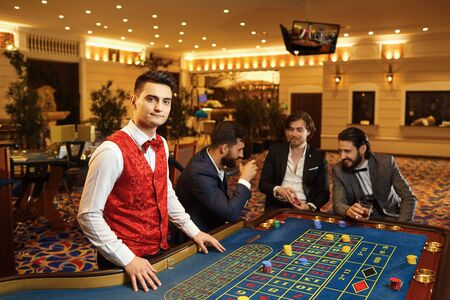 A croupier man works at a poker roulette table in a casino.