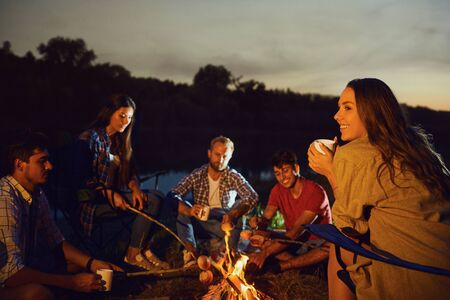 Girl with a mug of tea against the backdrop of friends by the bonfire at night in a forest on a picnic.