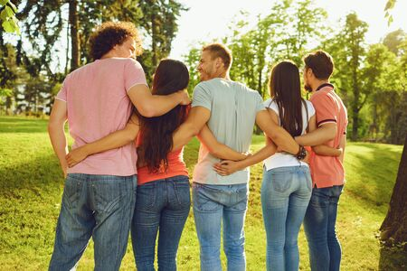 Groups of friends are embraced in the park in nature. Back view.