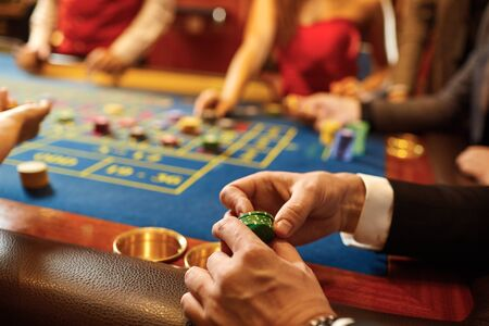 Chips in the hands of a man at a casino roulette poker table. The concept of gambling. Stockfoto
