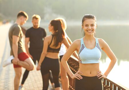 Young sporty girl smiles on the background of friends athletes in the park. Health. Healthy lifestyle.