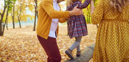 Family playing with their daughter on nature in the fall.