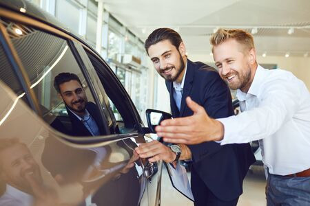 Auto business. Sale and rental of cars. Male buyer and buyer are looking at a new car. Stockfoto