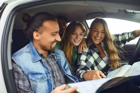 A group of happy friends travelers choose the route on the map ride in the car. Stockfoto