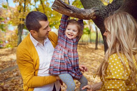 Happy family smiling playing in the park in the fall.