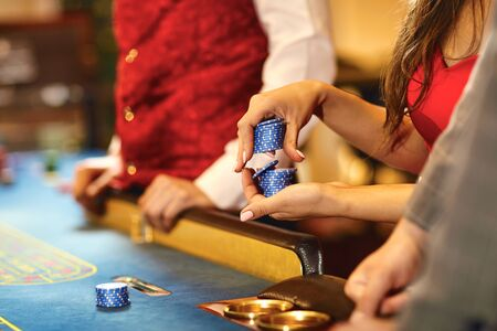 Hands of people with chips at poker roulette table gambling in a casino.