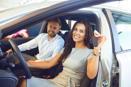 Una feliz pareja compró un auto nuevo en una sala de exhibición de autos. Compra y alquiler de coches.