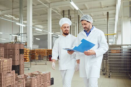 The technologist and baker speak in a bread factory. Factory workers in the workplace. Stockfoto