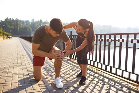Knee injury in a male athlete in a park. Girl athlete helps a person injured during exercise. Injury during training.